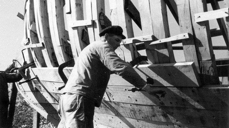 Två hantverkare jobbar med att bygga skrovet på en fiskebåt, byggd på Ringens Varv.