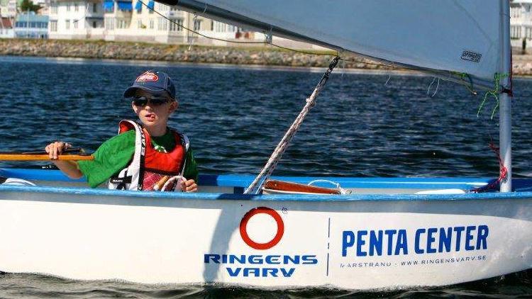 Bild på en pojke i en optimist, självklart med Ringens Varvs loggan på. Vad symboliserar sommaren bättre än närheten till havet från en optimist?