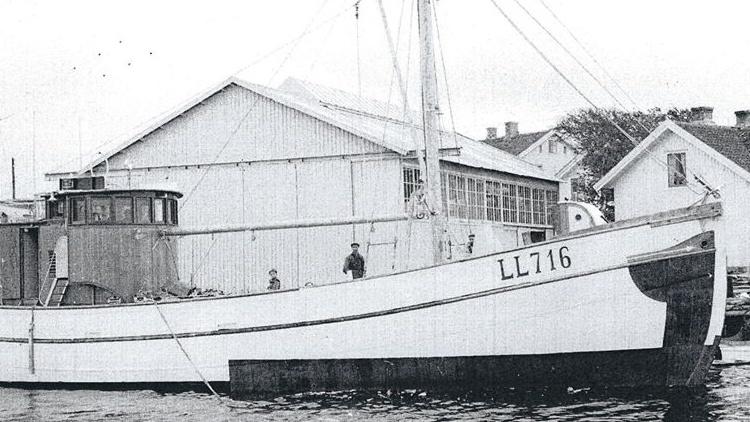 Fotografi av fiskebåt med Ringens Varvs produktionshallar i bakgrunden. Bilden är tagen på 1950-tal.